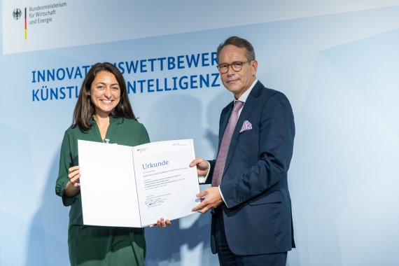 Claudia Salwiczek-Majonek is standing next to Secretary of State Dr. Ulrich Nussbaum wo presents the certificate.