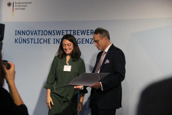 Claudia Salwiczek-Majonek is standing next to State Secretary Dr. Ulrich Nussbaum who presents the certificate.