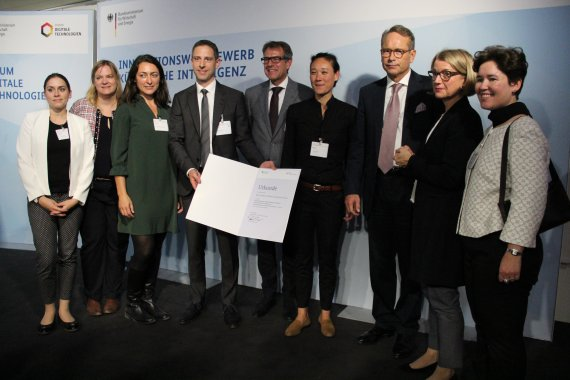Eight persons from the KIKS team as well as State Secretary Dr. Ulrich Nussbaum stand on stage and hold the certificate in front of the camera.